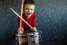 Teen Boy In Red Suit Playing Drum In Room. Child Holds Drumsticks