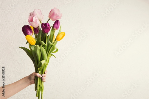 Fond de hotte en verre imprimé Fleur Hand holding tulips bouquet at white background, copy space