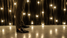 Close Up Photo Of A Man's Legs In Shoes On The Background Of Golden Light Bulbs In A Vertical Line Over Dark Texture