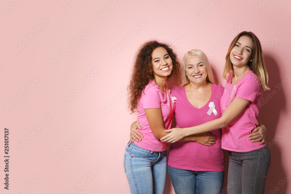 Fototapeta Group of women with silk ribbons and space for text on color background. Breast cancer awareness concept