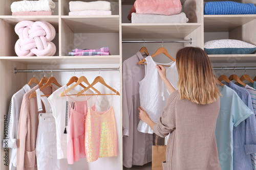 Valokuva Woman choosing outfit from large wardrobe closet with stylish clothes and home s