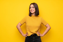 Young Woman Over Yellow Wall Posing With Arms At Hip And Smiling
