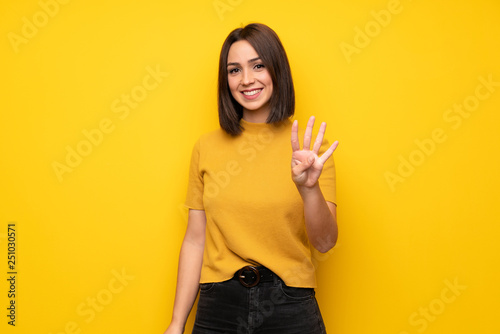 Young woman over yellow wall happy and counting four with fingers Tableau sur Toile