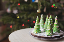 Cake Decorated With Christmas Trees On A Table By A Christmas Tree