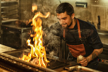 Bearded Handsome Man In Jeans Apron And With Tattoo On Hand Cooking. Chef Smiling, Holding Oil In Hand And Looking At Meat On Grill. Tasty Beef Steak Flaming With Fire And Smoke.