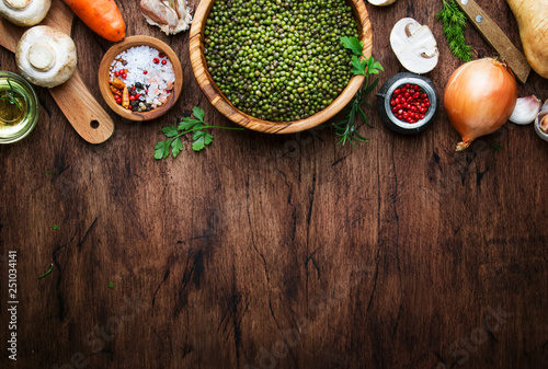 Ingredients for cooking green lentils with mushrooms and vegetables, spices and herbs, vintage wooden kitchen table, food cooking background, place for text. Vegan or vegetarian food - 251034141