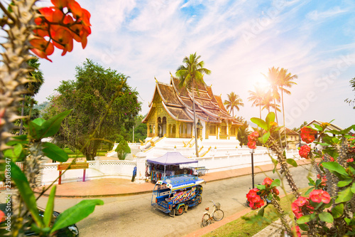 Photo Stunning view of a tuk tuk (auto rickshaw) passing in front of the beautiful Haw Pha Bang Temple with some blurred Dok Champa laos national flowers in the foreground