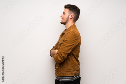 Fotomural  Handsome man over white wall in lateral position