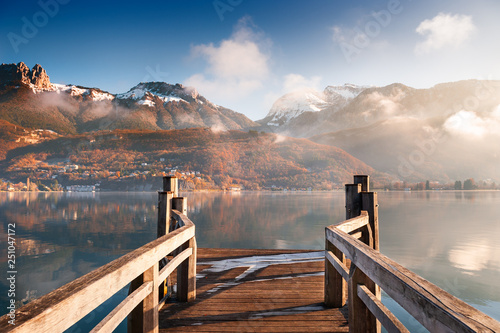 Wooden pier on Annecy lake in winter. Alps mountains, France. Canvas Print