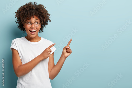Carta da parati  Beautiful black woman looks to side, shows free advertising space, smiles broadly, dressed in white casual t shirt, isolated over blue background, wears spectacles for good vision
