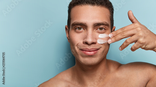 Fotografie, Obraz  Close up shot of attractive man with healthy skin, applies cream for anti wrinkl