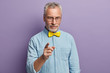 canvas print picture - Photo of attractive bearded man with grey hair and wrinkles, feels self assertive, points at you with fore finger, confirms to listen his advice, wears elegant shirt and bowtie, poses over lilac wall