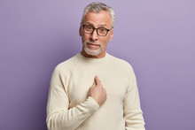 Are You Talking About Me? Bearded Senior Man Points At Himself With Bewilderment, Asks If He Did Something Wrong, Wonders, Wears Casual White Jumper And Spectacles, Isolated Over Purple Background