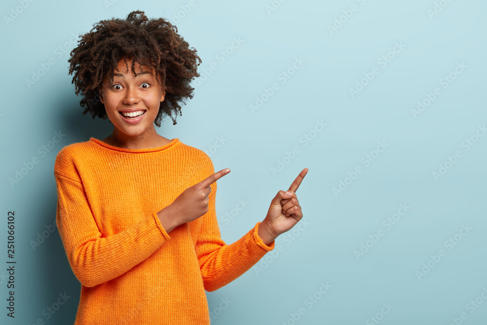 Fototapety, obrazy: Cheerful lovely young girlfriend with broad smile, shows white teeth, indicates with both fore fingers at blank space, wears orange jumper, isolated over blue wall. Buy this thing on discount or sale