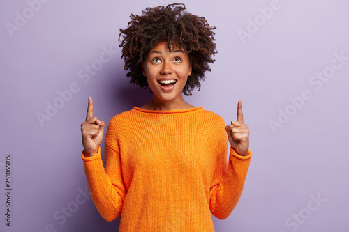 Fotografia Positive young good looking woman with Afro hairstyle, indicates with both index fingers, wears casual orange sweater, feels pleased, isolated over purple background
