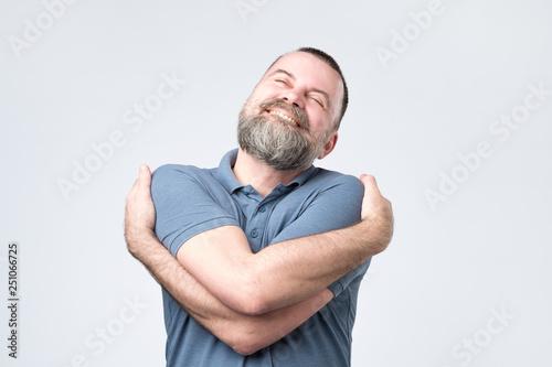 Photo  Funny selfish mature european guy in blue shirt cuddling himself
