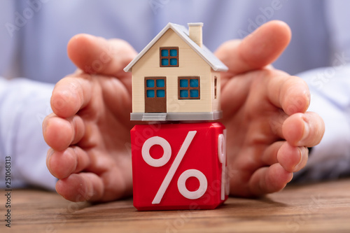 Person Protecting House Model Over Cube With Percentage Symbol Canvas Print
