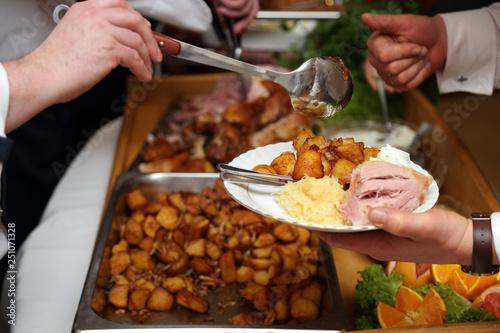 Kucharz kroi pieczone mięso na przyjęciu.