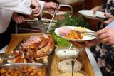Kucharz porcjuje pieczone mięso na przyjęciu.