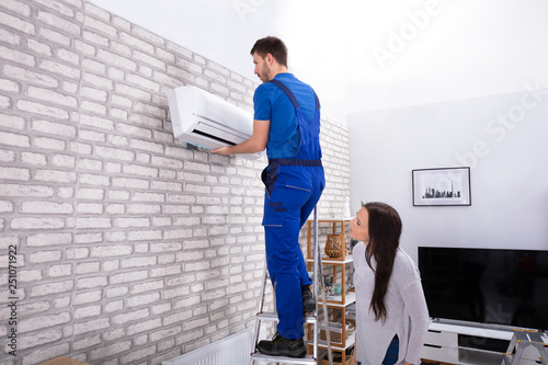 Male Technician Fixing Air Conditioner On Wall Canvas Print