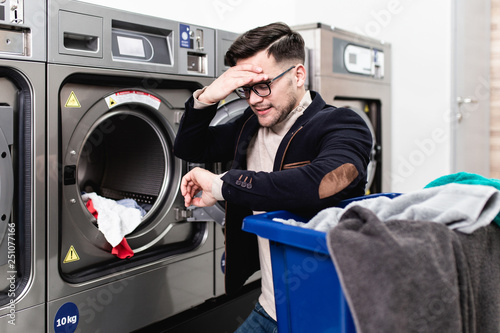 Handsome Young Businessman In A Hurry To Work Doing Laundry
