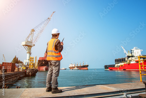 Fotografia, Obraz harbor master port control in command the ship to takes berthing to alongside the terminal docking, the ship assist pushing by tug boat safety to floating dock yard, dry dock alongside for repairing