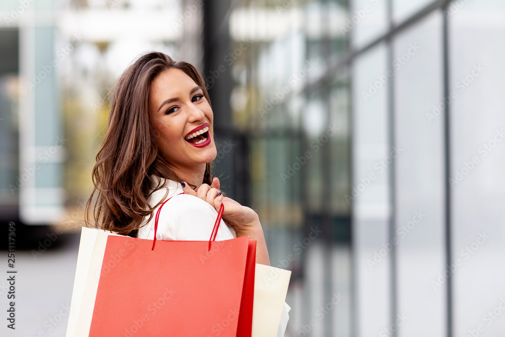 Fototapeta Beuatiful young long hair woman with shopping bags on her hands smile at the street