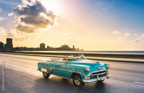 Vintage voitures Amerikanischer mint blauer Cabriolet Oldtimer auf dem berühmten Malecon im Sonnenuntergang in Havanna Kuba - Serie Kuba Reportage
