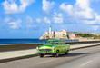 Amerikanischer grüner Cabriolet Oldtimer auf dem berühmten Malecon und im Hintergrund die Festung Castillo de los Tres Reyes del Morro in Havanna Kuba - Serie Kuba Reportage