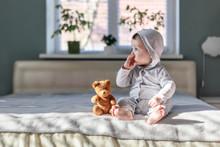 Happy Baby Boy In Grey Pyjamas On Bed In His Room