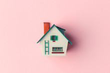 Plastic House Model On Pink Background. Real Estate Concept