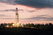 Oil Gas Drilling Rig On Sunset Background. Industrial Concept