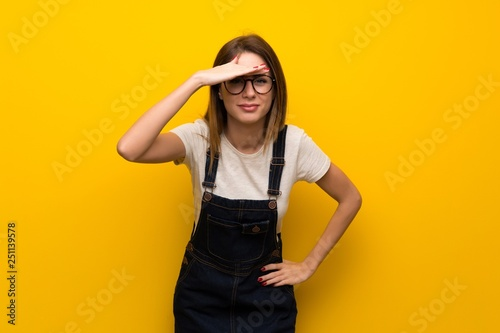 Woman over yellow wall looking far away with hand to look something
