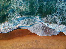 Aerial View Of Sandy Beach With Waves And Clear Ocean Water. Drone Photo
