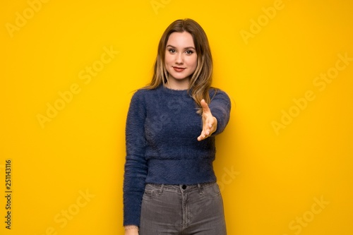 Teenager girl over yellow wall shaking hands for closing a good deal
