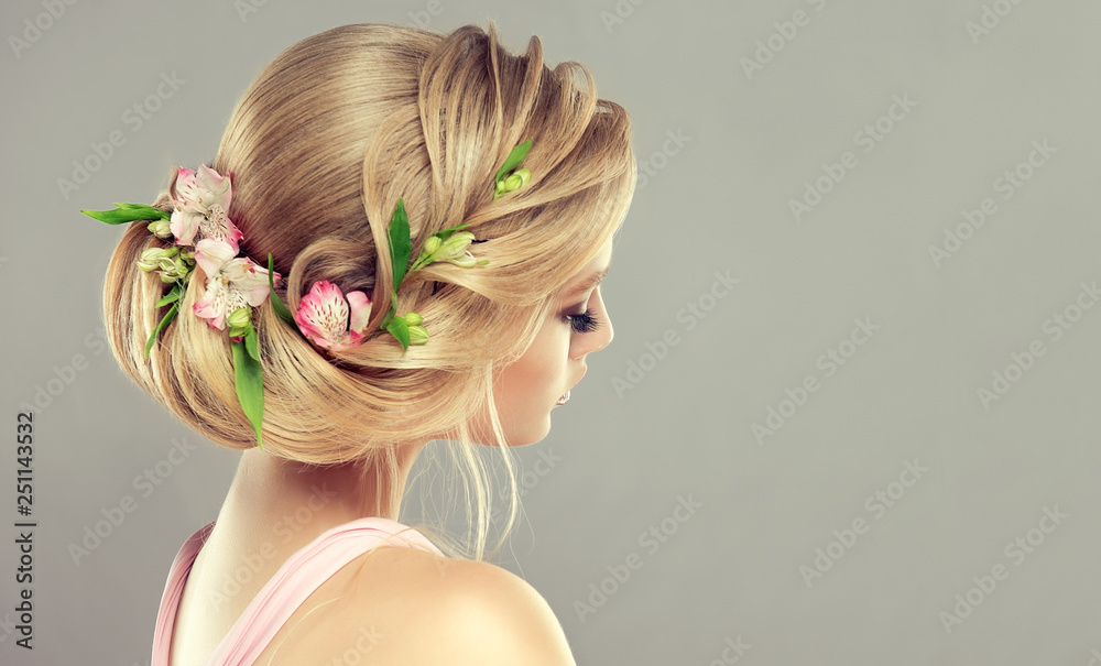 Fototapeta Beautiful model girl  with elegant hairstyle and rose flowers in a plait . Woman with fashion  spring hair.