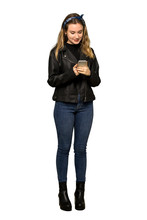 A Full-length Shot Of A Teenager Girl With Leather Jacket Sending A Message With The Mobile On Isolated White Background