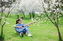Beautiful Happy Little Caucasian Girl Sitting On Green Grass Playing Denim Guitar In Spring Park