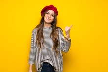 Girl With French Style Over Yellow Wall Pointing To The Side To Present A Product
