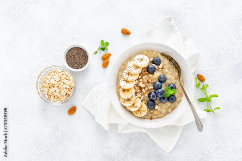 Fototapeta Healthy vegetarian food, oatmeal with fresh blueberry, banana, almond nuts and chia seeds for breakfast, view from above obraz