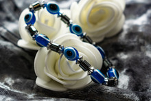 Blue Bracelet Made Of Natural Stones For Women's Day, March 8. Figure In The Form Of Eyes And Pupil From Evil Eye, Anger And Detractors. On Grey Velvet With White Roses.