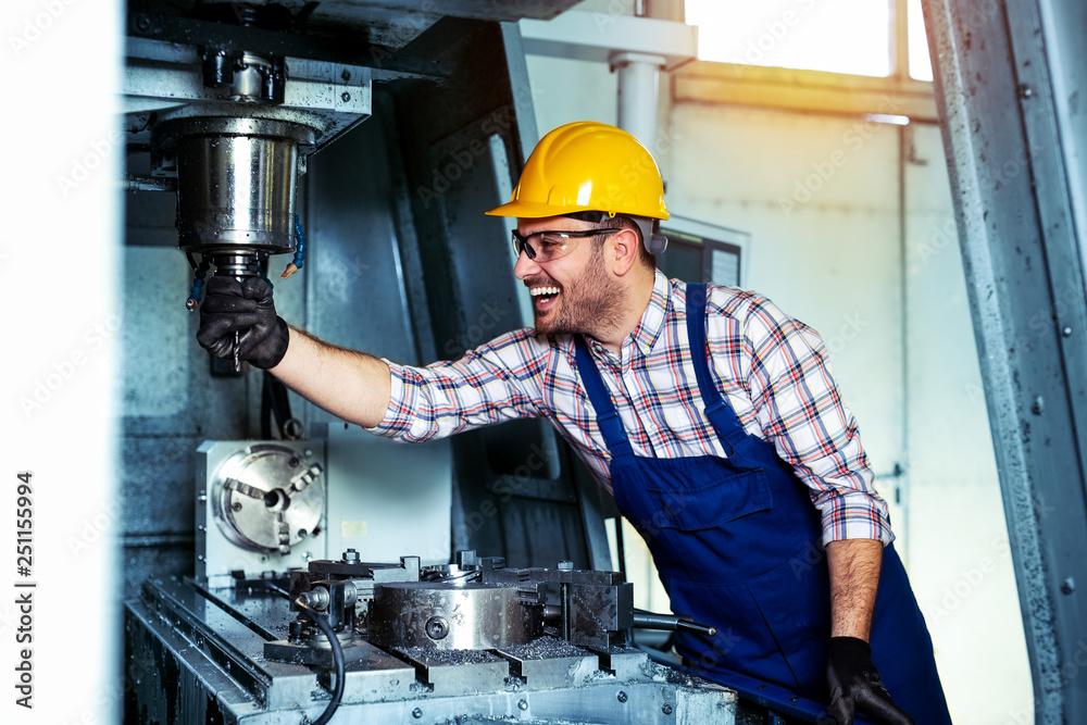 Fototapeta Mechanical technician worker of cnc milling cutting machine center at tool workshop manufacturing