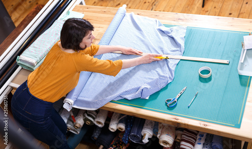 High angle view of female seller measuring textile