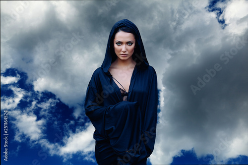 Fotomural Young beautiful woman with black hair and in the dark blue cloak with hood at th