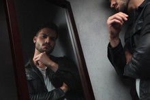 Pensive Young Man Looks In The Mirror
