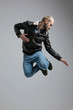 man in leather jacket and jeans jumping high into the air