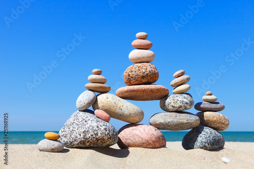 Photo sur Plexiglas Zen pierres a sable Rock zen pyramid of colorful pebbles on a sandy beach on the background of the sea. Concept of balance, harmony and meditation.