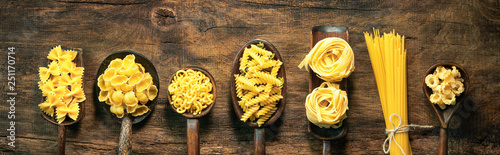 Tela Various pasta on spoons over wooden background