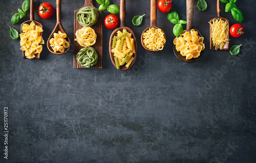 Fotografija Various pasta on wooden spoons over stone background