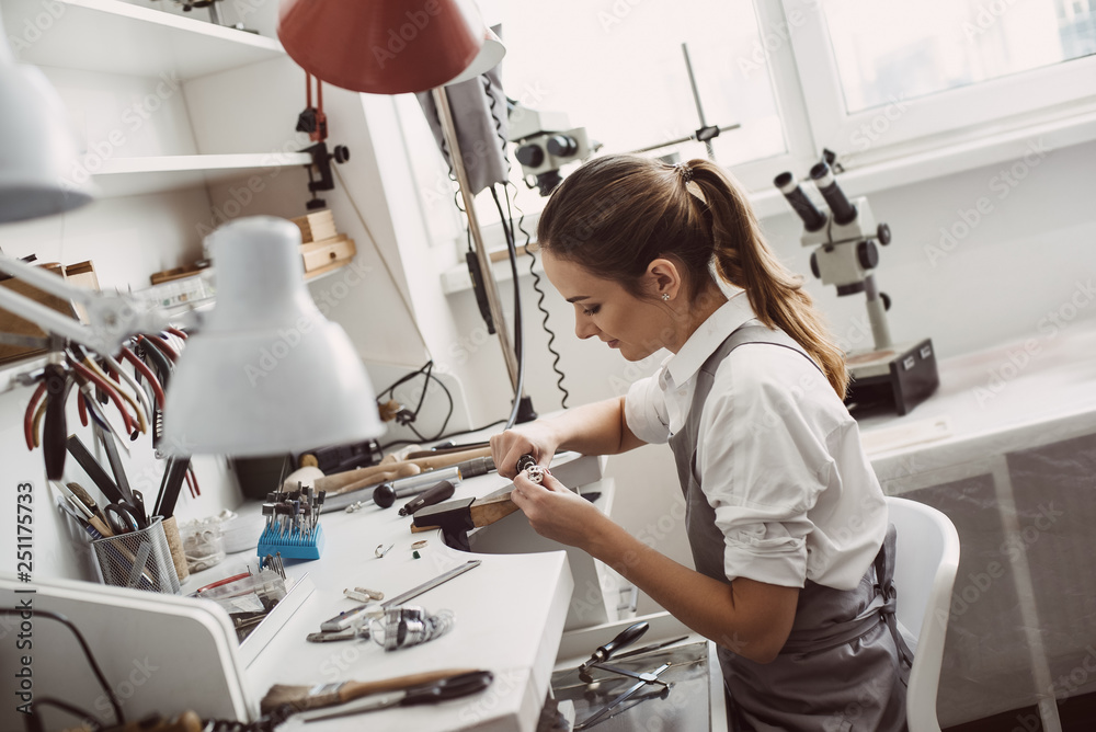 Fototapety, obrazy: All about work. Close up portrait of a female jeweler working on a ring at her workbench. Jewelry making process